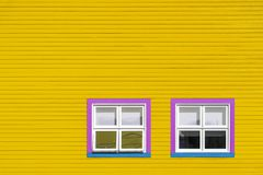 Pink and blue windows on yellow wall. Pink, blue and white windows on a yellow wooden wall. Minimalism style of the houses of Iles de la Magdalen, Canada, in royalty free stock image