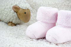 Pink bootees for babies with one toy sheep. On the white fur Stock Photography
