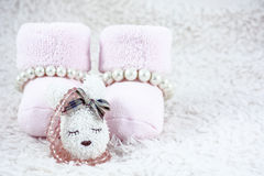 Pink bootees for babies with several bracelets and one brooch. On the white fur Stock Image