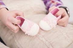 Pink booties for newborn baby in hands of dad. pregnancy Stock Photos