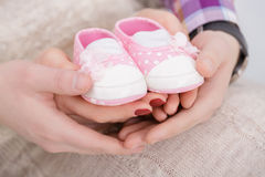 Pink booties for newborn baby in hands of mum and dad. pregnancy Stock Photo