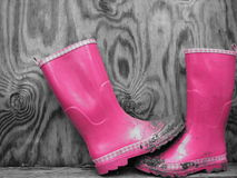 Pink Boots Black and White Background. Muddy pink rainboots with a black and white wood background Stock Images