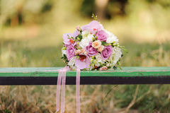 Pink Bouquet on Bench. Pink wedding bouquet on bench Royalty Free Stock Photo