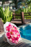 Pink bouquet. Pink color theme bouquet of roses and others on sun deck, blue swimming pool and green garden background Royalty Free Stock Photography