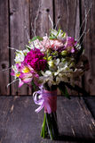 Pink bouquet from gillyflowers and alstroemeria on old wooden ba Royalty Free Stock Image