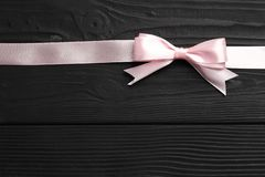 Pink bow and ribbon on black wooden background royalty free stock photos