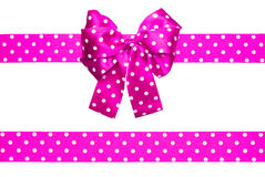 Pink bow and ribbon with white polka dots made from silk Stock Image