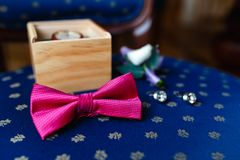 Pink bow tie, beautiful glass cufflinks, flower boutonniere. A men's set of accessories on an old wooden chair with a soft blue s. Eat. Set of accessories for a Stock Image