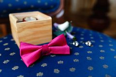 Pink bow tie, beautiful glass cufflinks, flower boutonniere. A men's set of accessories on an old wooden chair with a soft blue s. Eat. Set of accessories for a Stock Photo