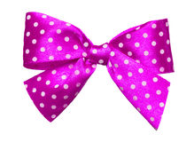 Pink bow with white polka dots made from silk. Isolated royalty free stock image