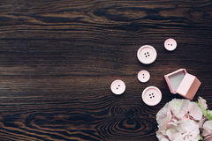Pink box for engagement ring, Buttons and hydrangea on wooden table, top view. Space for text Stock Photo