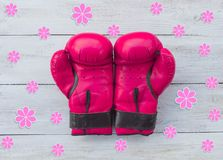Pink boxing gloves and flowers on a wooden background, top view. 