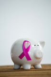 Pink Breast Cancer Awareness ribbon on piggybank over wooden table. Against white background Royalty Free Stock Photo