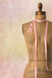 Pink breast cancer ribbon on mannequin. Dress form with vintage background