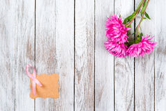 Pink breast cancer ribbon and pink flowers on wooden background. Pink breast cancer ribbon and pink flowers on the wooden background Stock Photography