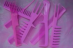 Pink bright comb for hairdressers. Beauty saloon. Tools for hairstyles. Colorful pink background. Barbershop. A set of different royalty free stock images