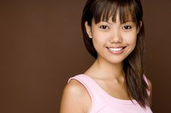 Pink On Brown 10. A cute young asian woman in a pink top on brown background Royalty Free Stock Photos