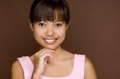 Pink On Brown 4. A cute young asian woman in a pink top on brown background Stock Images