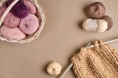 Pink and brown knitting wool and knitting on knitting needles on beige background. Top view. Copy space. Pink and brown ball wool and knitting on needles on Stock Photos