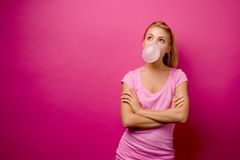 Pink Bubble - Horizontal. Girl in pink, blowing a big bubble against a pink background stock photo