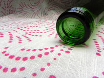 Pink bubbles spilling out of green bottle. Green bottle on cloth napkin, with dots appearing as spilling sparkling bubbles. Horizontal shot Stock Photography