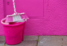 Pink bucket and a mop standing near a pink wall Stock Photos