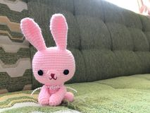 Pink bunny crochet doll in soft focus. Royalty Free Stock Image