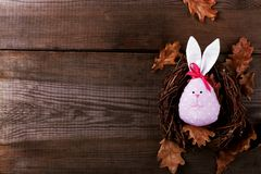 Pink Bunny Easter egg handmade with pretty face lying in a nest on a wooden background. Copy space royalty free stock image