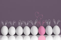 Pink bunny among white rabbits as Easter eggs stock photography