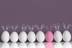 Pink bunny among white rabbits as Easter eggs royalty free stock images