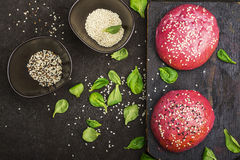 Pink buns for the vegetable Burger on the basis of beet with sesame seeds on dark background. Top view.  stock photos