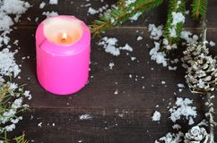 Pink burning candle with christmas decoration, fir tree, baubles and ribbon, in front of a white wooden wall or stock photography