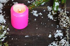 Pink burning candle with christmas decoration, fir tree, baubles and ribbon, in front of a white wooden wall or stock photos