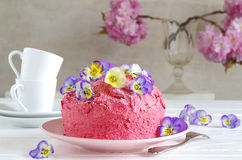 Pink butter-cream cake with horned pansy. A homemade pink butter-cream cake with horned pansy stock image