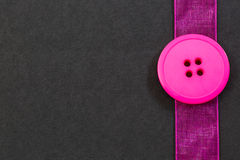 Pink Button and Ribbon on Black. Bright pink button and sheer ribbon border on a black paper background Stock Photo