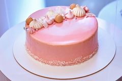 Pink cake with marshmallows and cupcakes on a plate stock photo