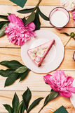 Pink cake on plate with pink peonies and milk Royalty Free Stock Images