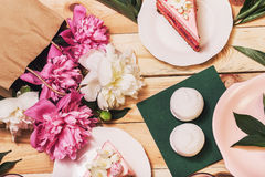 Pink cakes, zephyr on green napkins with big peonies Royalty Free Stock Photography