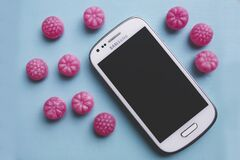 Pink candies and white smartphone Stock Images