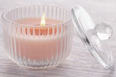 Pink candle burning in a glass beaker on an old white wooden table stock photo