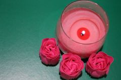 A pink candle burns in a glass. Nearby there are three pink buds. A burning candle creates a romantic atmosphere Stock Photo