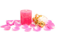 Pink candle with rose leaves and box of chocolate Royalty Free Stock Images