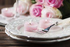 Pink candle and roses on the table Stock Photography