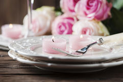 Pink candle and roses on the table Stock Photo