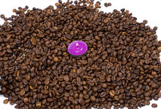The pink candle surrounded with coffee grains Royalty Free Stock Images