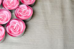 Pink candles are large in the left corner of the screen in the form of roses to the day of St. Valentine on a background of beige Royalty Free Stock Photos