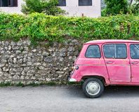 Pink car near an old brick wall Royalty Free Stock Photo