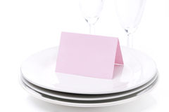 Pink card for congratulation on a plate and empty glasses Royalty Free Stock Photo