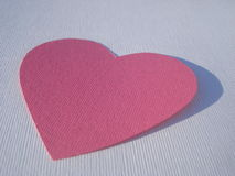 Pink cardboard heart on white Stock Photos