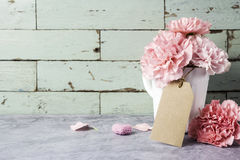 Pink carnation flower in white cup with blank brown paper tag an. D heart Stock Photos